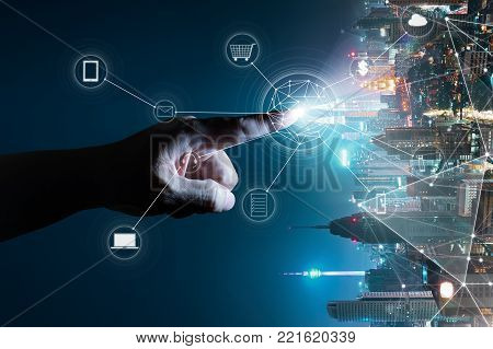 Unknown hand touching the light came out from the ground ,flip modern city background with wireless network connection concept , abstract communication technology image visual .