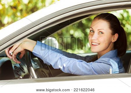 Happy girl driver smiling to you from the car