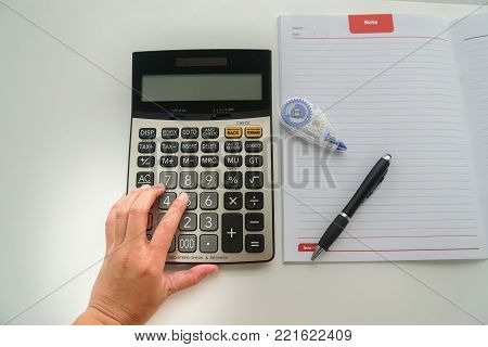 top view close up accountant with calculator, pen and correction fluid for tax and company income calculation