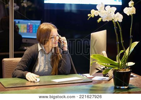 Hotel administrator. A woman-reception worker accepts an order for booking a room by phone. Profile shot of attractive executives at the reception of a hotel. The concept of service.
