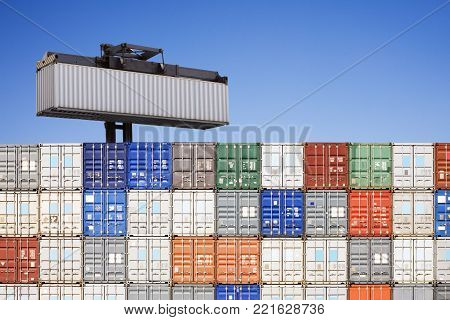 Stacked shipping containers, and one being held above. Concepts of rising above the crowd, being better than the rest, These are normal used shipping containers, tidy and cleaned up, but not perfect.