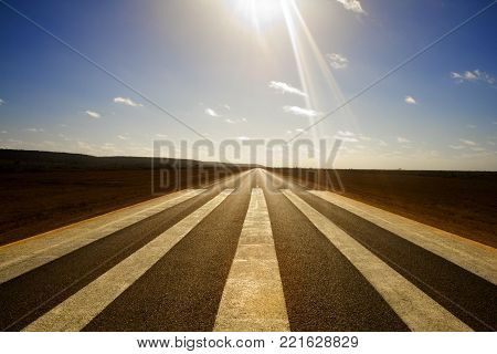 Wide angle shot of long straight road with runway markings and sun in picture causing lens flare. Eyre Highway, Nullarbor Plain, Western Australia. Used as emergency runway by flying doctor.
