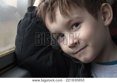 Boy at the window smiling portrait. Good mood toddler in the train.