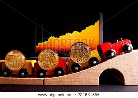 ICO Initial coin offering method of funding startups vs IPO. A toy train carries coins as a symbol of cashflow for funding startup. In the background are quotes electronic currencies.