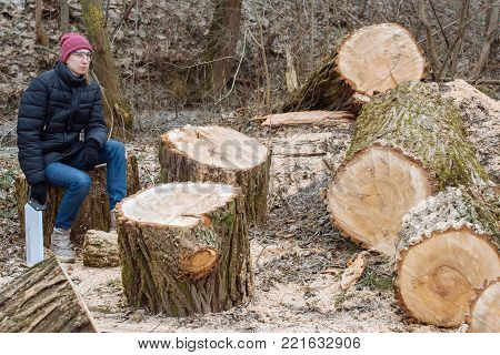 Hard work done: young woman saws a huge tree in the forest and sits resting with a saw in her hand