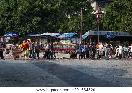 Yangshuo, China - August 3, 2012: A traditional funeral parade in a street of the town of Yangshuo in China