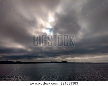 Storm clouds over the ocean with mountain in the background