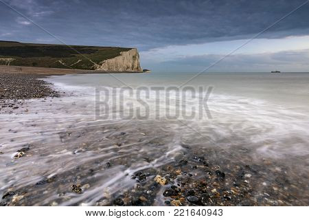 Sea and pebbles in Cuckmere Haven with the Seven Sisters cliffs