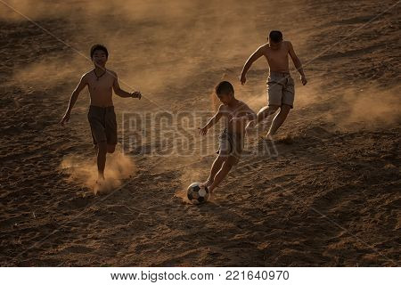 Asia children playing football at the countryside.