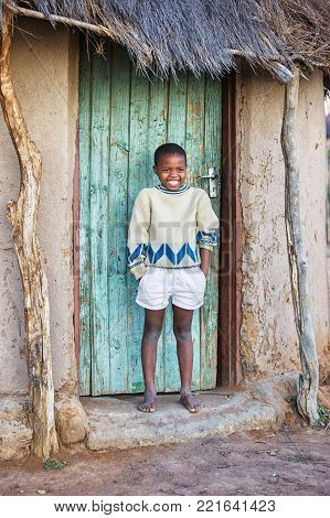 african Motswana child sitting in the door of the shack
