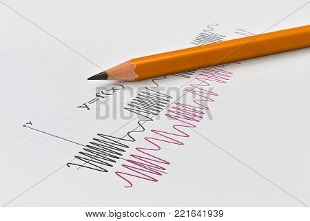 Closeup of the graph of two math functions and yellow pencil