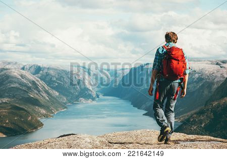 Man traveler with red backpack hiking Travel Lifestyle concept adventure outdoor active summer vacations in Norway tourist sightseeing Lysefjord alone