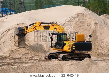 The excavator works against a background of a pile of sand.