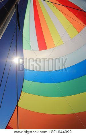 The wind has filled the spinnaker on sailing yacht. Detail of a colorful sail against the deep blue sky.