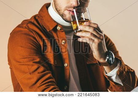 partial view of man in stylish clothing with glass of whiskey in hand isolated on beige