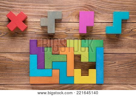 IQ test. Choose correct answer. Logical tasks composed of colorful wooden shapes, top view. Children's educational logical task, flat lay. Visual conundrum, find the missing piece of the proposed..