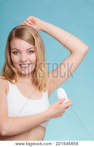 Daily skin care and hygiene. Girl applying stick deodorant in armpit. Young woman putting antiperspirant in underarms on blue