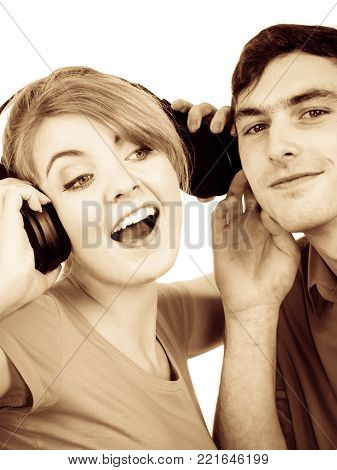 Couple two friends with big headphones listening to music mp3 together. Joyful happy woman and man on white. People leisure happiness concept. Filtered photo