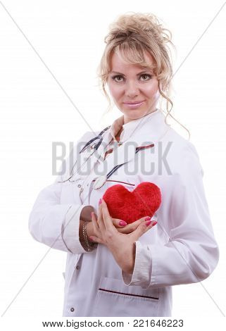Periodic examinations. Cardiology concept. Female cardiologist holding red heart. Middle aged doctor with stethoscope and white medical apron uniform. Isolated on white.