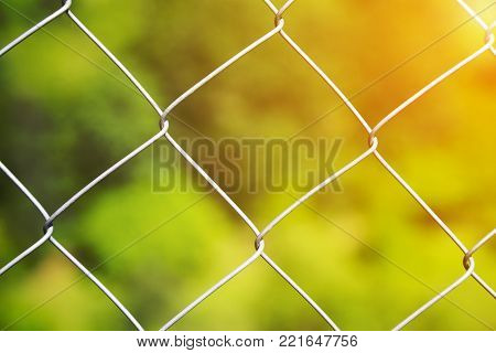 Detail of a diamond mesh wire fence with selective focus to the steel wire over a blurred green background with golden glow from the sun