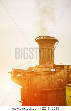 Front part of old locomotive with working engine with golden glow from the sun.
