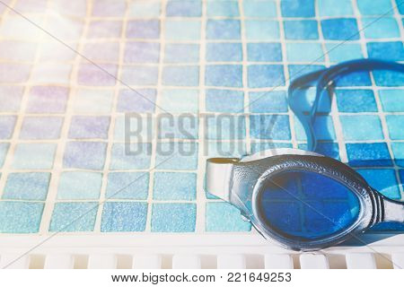 Part of a swimming pool goggles on the poolside with golden glow from the sun.