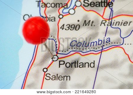 Close-up of a red pushpin in a map of Portland, USA.