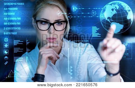 Suspicious. Smart experienced qualified programmer feeling worried while sitting with her fingers touching the chin and looking attentively at the transparent screen in front of her