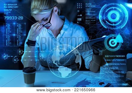 So tired. Young hardworking qualified programmer feeling tired and closing her eyes while sitting at the table with a glass of coffee on it