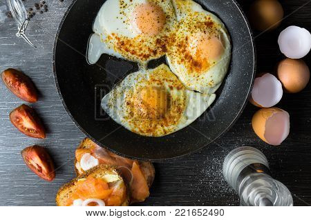 Delicious egs in pan with salmon, onion and tomatoes