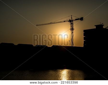 Silhouette image -  Derrick for the construction of the building at sunset.