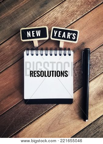 New year's resolutions concept. On wooden table background with wooden decorative clips and a pen.