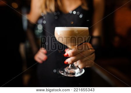 girl in a black dress and with red manicure holding in her hands one goblet with an alcoholic cocktail sour mix