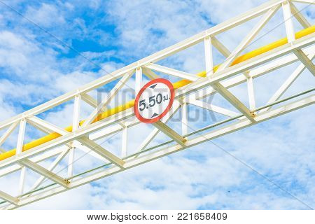 Height Restriction limit Sign on pipe rack, white metal sign on steel structure with blue sky