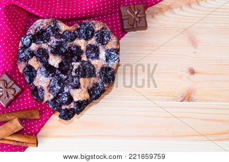 a heart-shaped pie of cherries on a wooden background and a series of chocolate-shaped heart-shaped and cinnamon sticks