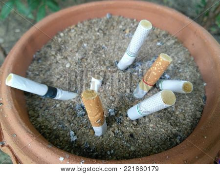cigarette stub on the sand in the ashtray