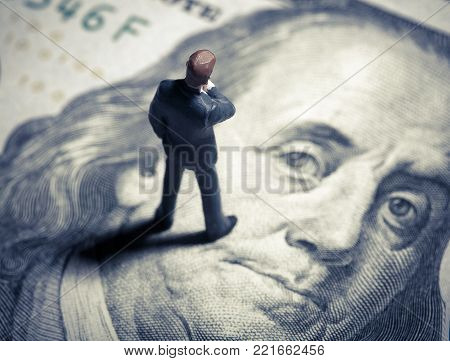 Miniature figurine businessman with 100 dollars. Top view. Focus on the head