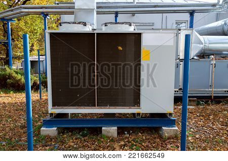 Industrial cooling unit for central ventilation system with air handling unit unit standing outdoor on the ground covered by fallen leaves