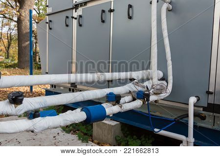View of the insulated refrigerant pipelines with thermal expansion valves and automation sensors connected to the industrial air handling unit