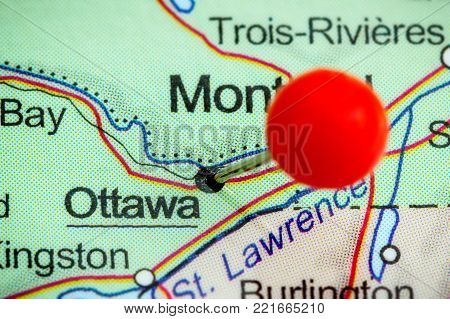Close-up of a red pushpin on a map of Ottawa, Canada.