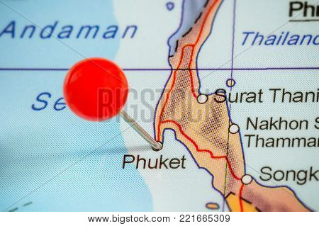 Close-up of a red pushpin on a map of Phuket, Thailand.