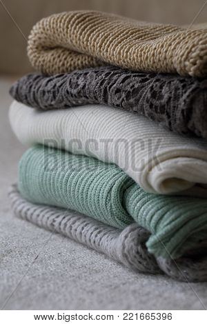 A stack of knitted garments on a shelf in the closet