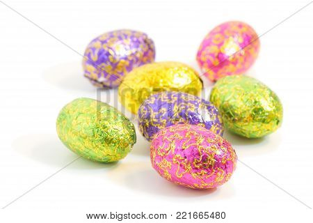 Close-up of several chocolate Easter eggs in colorful wrappings isolated on white background.