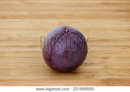 Close-up of a whole passion fruit (passionfruit, purple granadilla (Passiflora edulis)) on a wooden table.