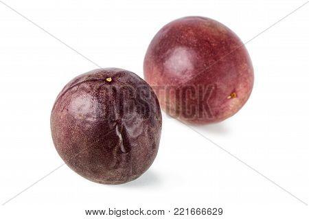 Close-up of two whole passion fruits (passionfruit, purple granadilla (Passiflora edulis)) isolated on white background.