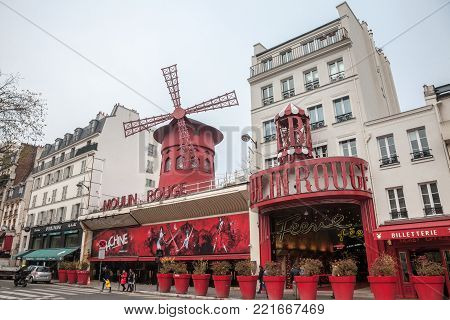 PARIS, FRANCE - DECEMBER 19, 2017: Moulin Rouge cabaret taken during a cloudy afternoon in the red light district of Paris, Moulin Rouge is one of the most known cabarets of Paris, famous for creating can can dance