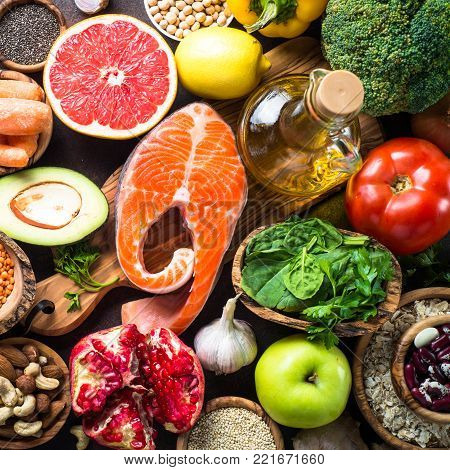 Balanced diet food background. Organic food for healthy nutrition, superfoods. Fish, legumes,  nuts, seeds, greens, oil and vegetables Top view