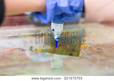 art equipment, tools, crafting concept. close up of the tip of tube of acrylic paint, that is smeared with blue paint, arms of artist in blue work gloves are holding it carefully