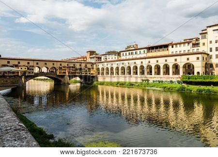 View on famous Ponte Vecchio bridge from the other side of the Arno river in Florence, Italy, with buildings reflecting in the water