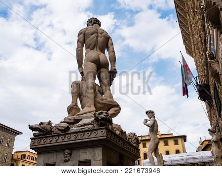 Back view of the statue of Hercules and Caco by Baccio Bandinelli in front of the Palazzo Vecchio in Florence, Italy. In the background the famous David.